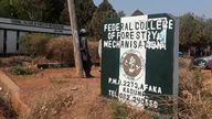 A man rests on a pole beside the signage of the Federal College of Forestry Mechanization where gunmen abducted students,
