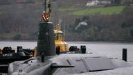 Crew from HMS Vengeance, a British Royal Navy Vanguard class Trident Ballistic Missile Submarine, stand on their vessel as they return along the Clyde river to the Faslane naval base near Glasgow, Scotland December 4, 2006. REUTERS/David Moir/File Photo