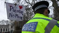 A police officer looks on as demonstrators gather during a protest in Parliament Square in London, Sunday, March 14, 2021. London's Metropolitan Police force was under heavy pressure Sunday to explain its actions during a vigil for Sarah Everard whom one of the force's own officers is accused of murdering. (AP Photo/Alberto Pezzali)