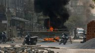 Armed riot policemen and soldiers reach a makeshift barricade made by anti-coup protesters in Mandalay. Pic: AP