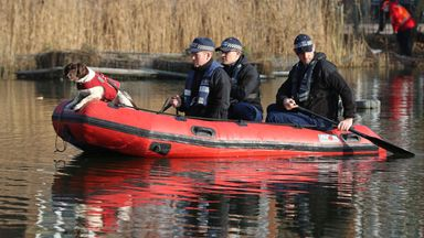 Police in a RIB with a sniffer dog search a pond on the common