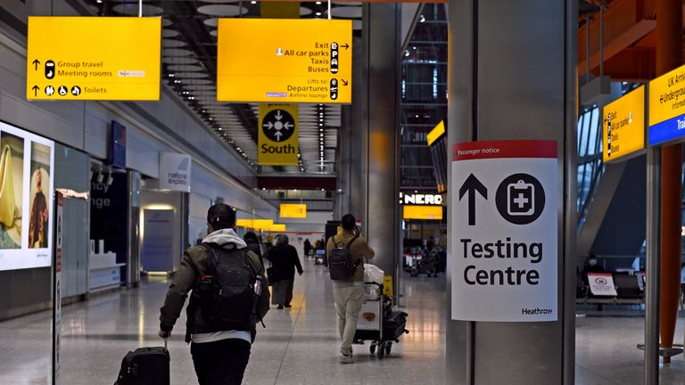 A passenger walks past a sign for the covid testing centre in the Arrival Hall of Terminal 5 at London's Heathrow Airport after arriving into the UK following the suspension of the travel corridors. Passengers arriving from anywhere outside the UK, Ireland, the Channel Islands or the Isle of Man must have proof of a negative coronavirus test and self-isolate for 10 days. Picture date: Monday January 18, 2021.