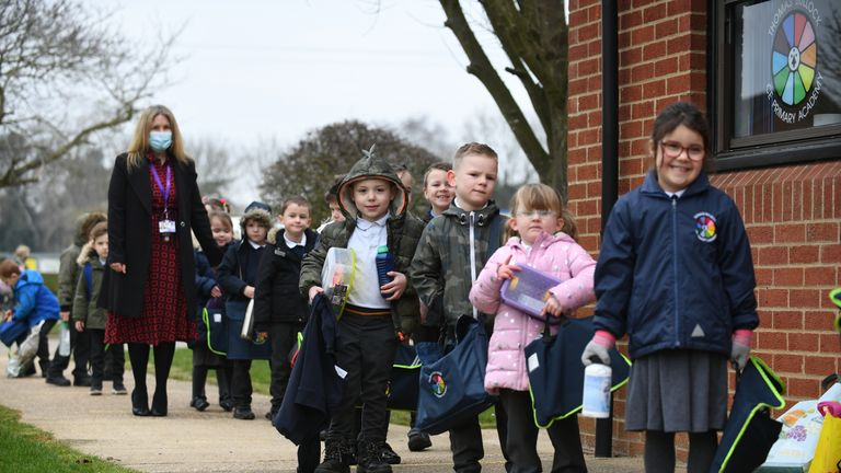 Children line up to enter the Thomas Bullock Church of England Primary Academy in Shipdham in Norfolk, as pupils in England return to school for the first time in two months as part of the first stage of lockdown easing. Picture date: Monday March 8, 2021.