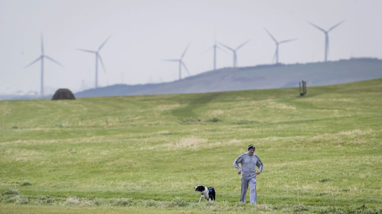 File photo dated 15/10/17 of man walking his dog near Whitehaven in Cumbria. Approved plans for a new coal mine near the Cumbrian town will produce more emissions than any of the others currently open in the UK, a climate group has warned. Issue date: Saturday January 30, 2021.