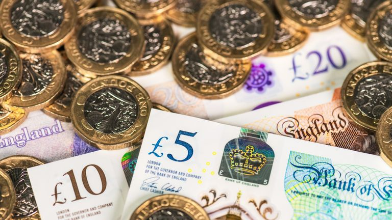 Recently issued UK £5, £10 and £20 polymer banknotes with £1 coins.