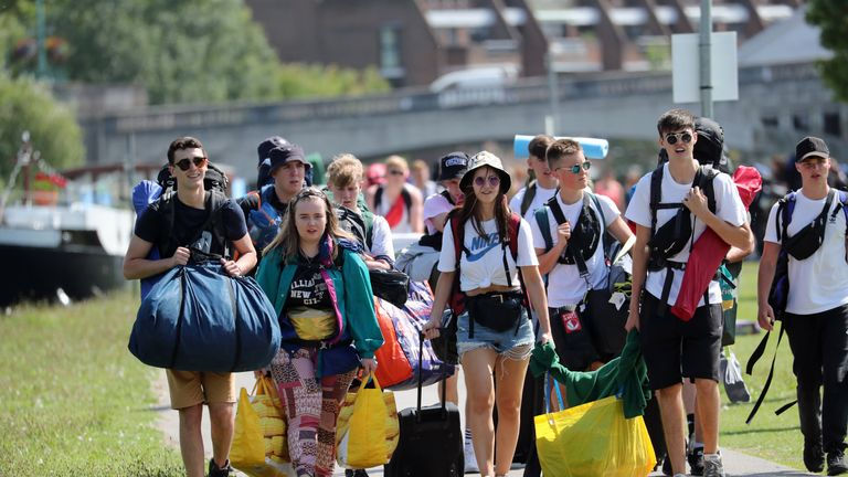 Festival goers walk along the towpath of the River Thames as they arrive for the Reading Festival at Richfield Avenue.