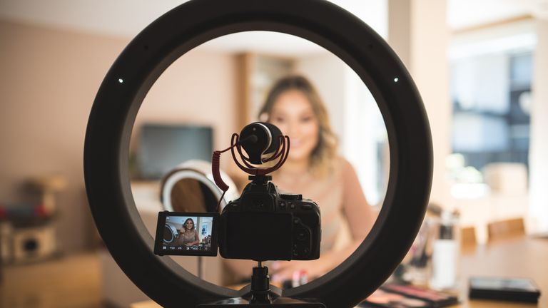 A young woman vlogging herself doing makeup