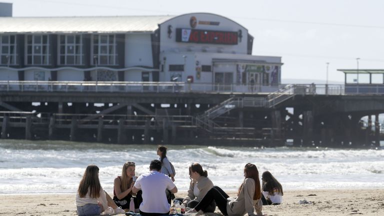 People sit on Bournemouth beach following the easing of England's lockdown to allow far greater freedom outdoors. Picture date: Monday March 29, 2021.