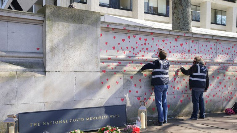 People painting red hearts on the COVID-19 Memorial Wall opposite the Houses of Parliament at Embankment, central London, in memory of the more than 145,000 people who have died in the UK from coronavirus. Picture date: Monday March 29, 2021.