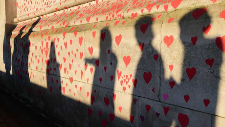 People are silhouetted against the COVID-19 Memorial Wall on the Embankment, central London, which has been painted with hearts in memory of the more than 145,000 people who have died in the UK from coronavirus. Picture date: Monday March 29, 2021.