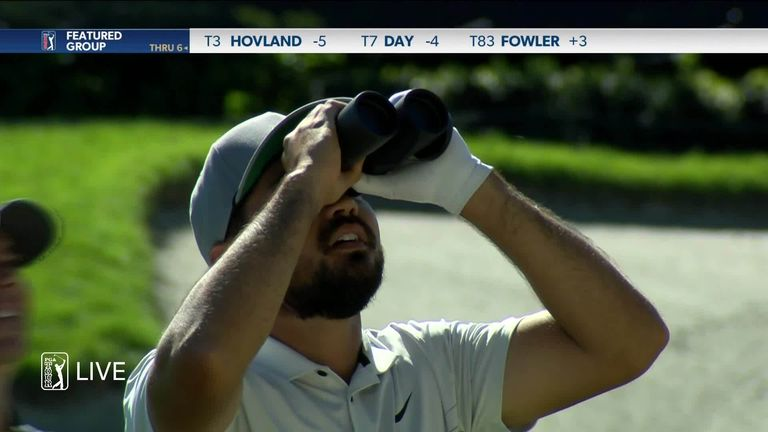 Jason Day gets help from a photographer to identify his ball in a bird's next at