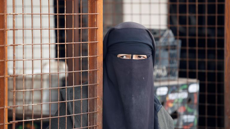 A woman looks out at al Hol camp in Syria