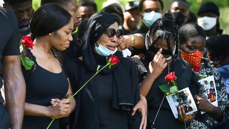 Khafi Kareem (left) and Victoria Oloniluyi (centre), the sister and mother of Alexander Kareem, prepare to lay roses on his coffin