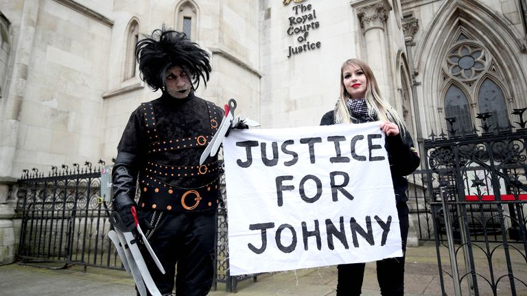 Supporters of Johnny Depp, one dressed as Edward Scissorhands played by Depp in the Tim Burton 1990 film of the same name, wait outside the Royal Courts of Justice in London, ahead of a ruling on Depp's application to the Court of Appeal. Mr Depp is asking for permission to appeal against a damning High Court ruling which found that he assaulted his ex-wife Amber Heard and put her in fear for her life. Picture date: Thursday March 18, 2021.