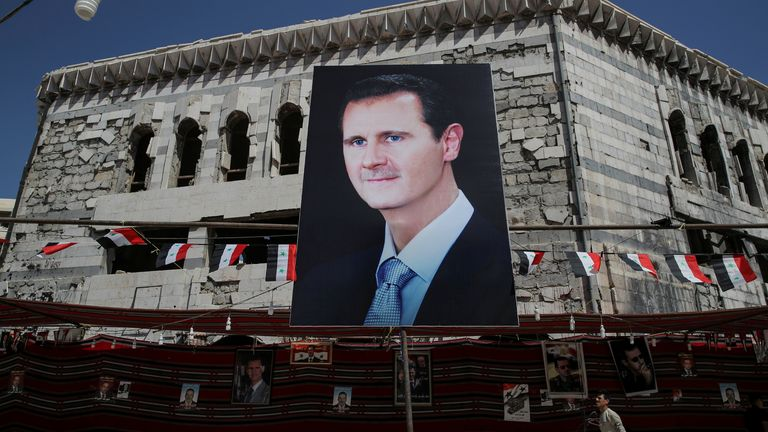 A man walks past a banner depicting Syrian president Bashar al-Assad in Douma, outside Damascus, Syria, September 17, 2018