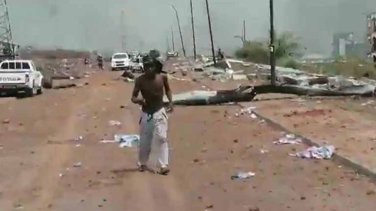 People run through the rubble to escape the explosions