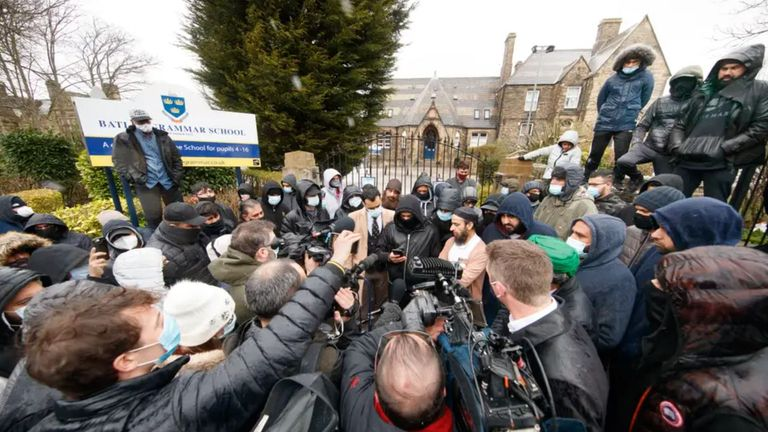 Protesters and media surround the school gates on Friday