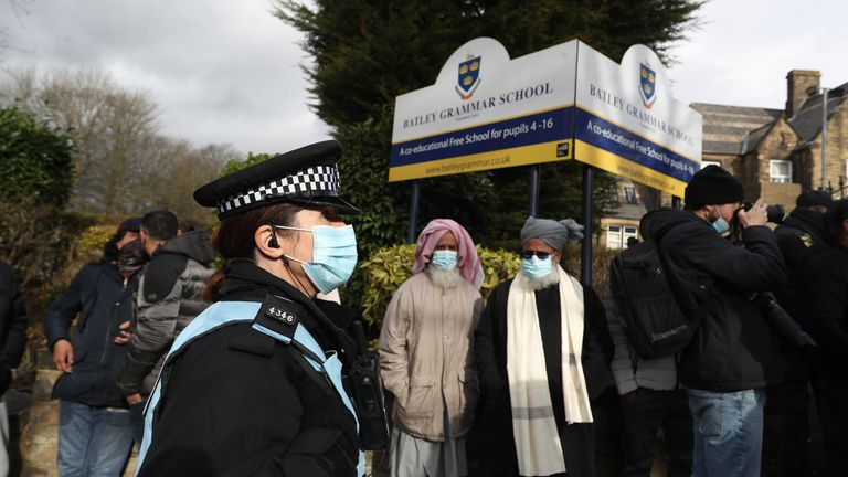 A police officer observes protesters gathered outside Batley Grammar School in Batley, West Yorkshire, where a teacher has been suspended for reportedly showing a caricature of the Prophet Mohammed to pupils during a religious studies lesson. Picture date: Friday March 26, 2021.