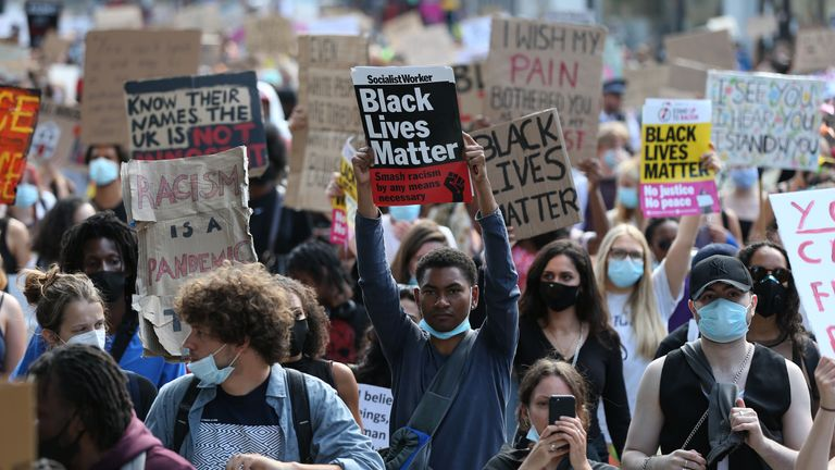 People during Black Lives Matter rally walk along Victoria Street in London
