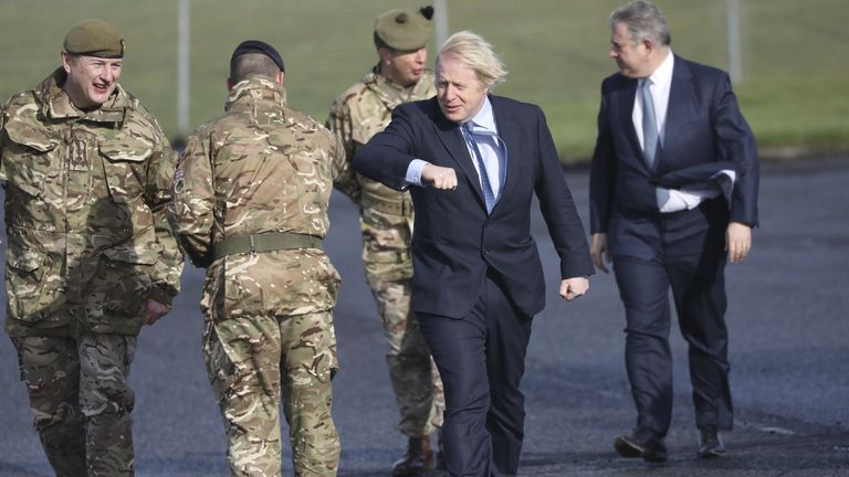 Prime Minister Boris Johnson greets troops alongside Northern Ireland Secretary Brandon Lewis (right) and Brigadier Chris Davies, Commander 38 (Irish) Brigade (left), during a visit to Joint Helicopter Command Flying Station Aldergrove in Northern Ireland