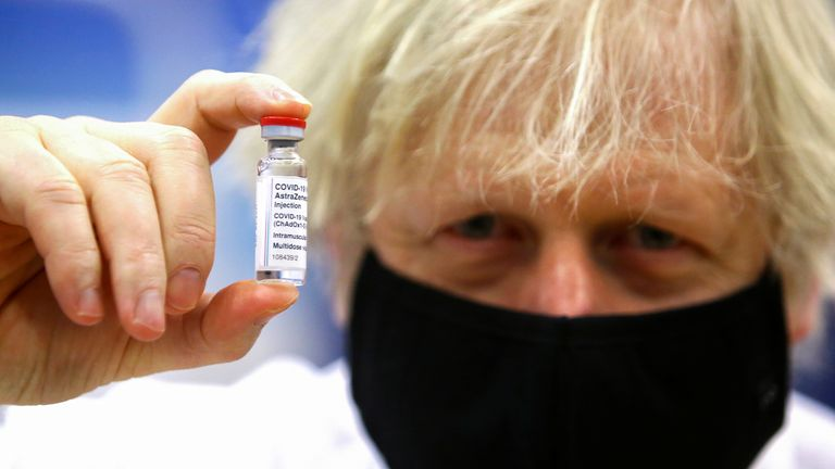 Britain's Prime Minister Boris Johnson holds a vial of an Oxford-AstraZeneca COVID-19 vaccine, during his visit at a vaccination centre at Cwmbran Stadium in Cwmbran, south Wales, Britain February 17, 2021. Geoff Caddick/Pool via REUTERS
