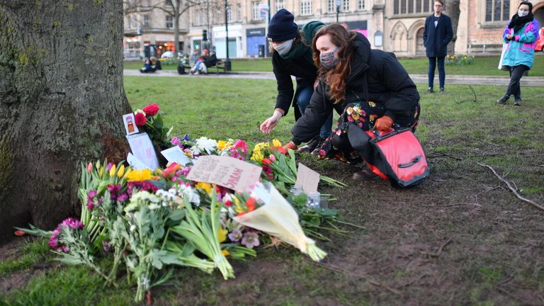 People places flowers at a tree on College Green in Bristol after the Reclaim These Streets vigil for Sarah Everard was officially cancelled. Serving police constable Wayne Couzens, 48, has appeared in court charged with kidnapping and killing the marketing executive, who went missing while walking home from a friend's flat in south London on March 3. Picture date: Saturday March 13, 2021.