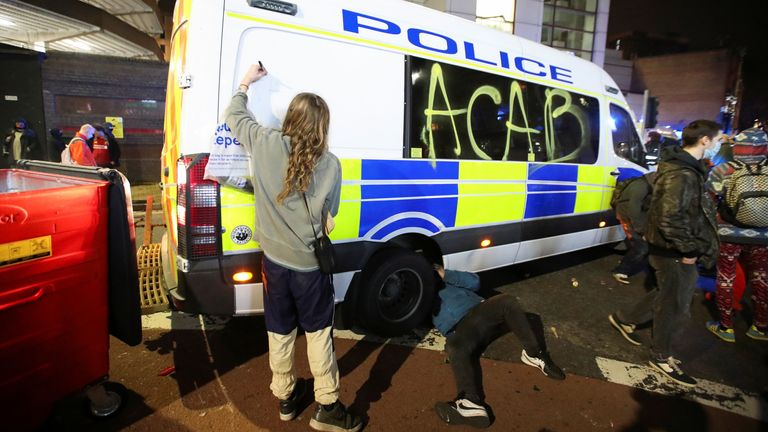 A demonstrator graffitis a police vehicle