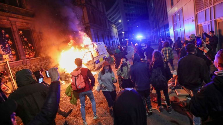 Demonstrators stand near a burning police vehicle