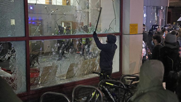Protester breaks smashes a window with a stick outside Bridewell Police Station