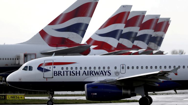FILE PHOTO: A British Airways plane taxis past tail fins of parked aircraft near Terminal 5 at Heathrow Airport in London, Britain, March 14, 2020