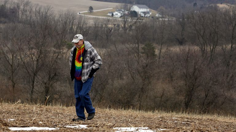 Mike Carpenter, the uncle of Greg Longenecker, walks in the filed where the man was killed by a bulldozer. Pic: AP
