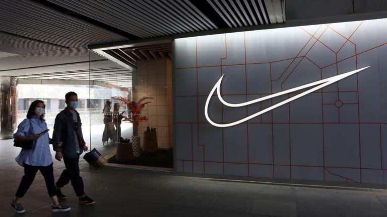 People walk past a Nike store in Beijing