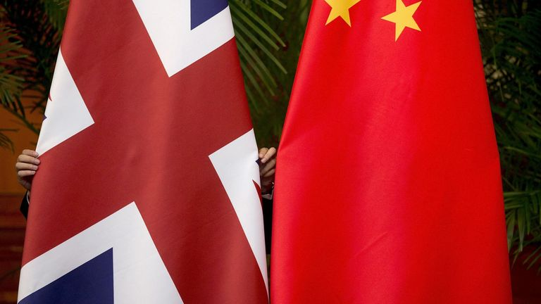 "FILE PHOTO: A worker adjusts British and China (R) national flags on display for a signing ceremony at the seventh UK-China Economic and Financial Dialogue ""Roundtable on Public-Private Partnerships"" at Diaoyutai State Guesthouse in Beijing, China September 21, 2015. REUTERS/Andy Wong/File Photo"