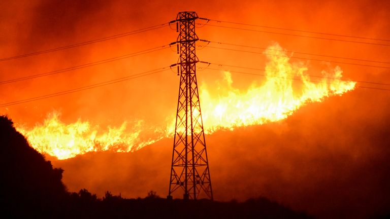 FILE PHOTO: A wind-driven wildfire burns near power line tower in Sylmar, California, U.S., October 10, 2019. REUTERS/Gene Blevins/File Photo