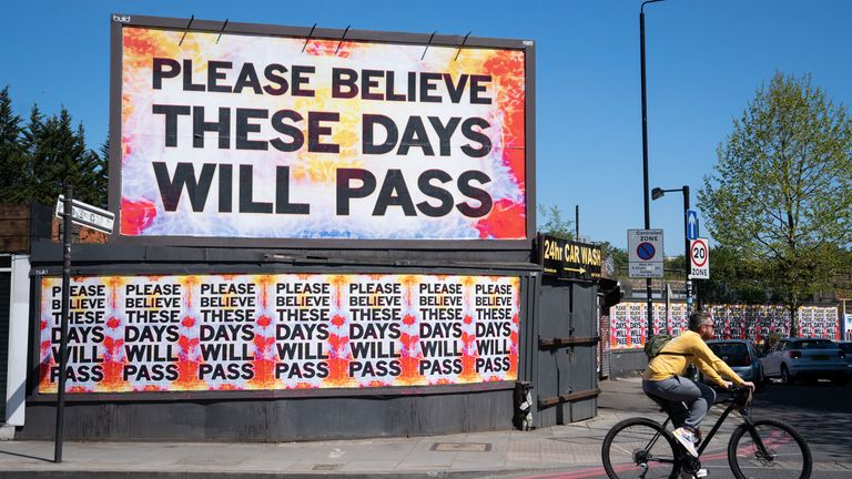 A cyclist rides past a billboard reading 'please believe these days will pass' in Shoreditch, east London, as the UK continues in lockdown to help curb the spread of the coronavirus.