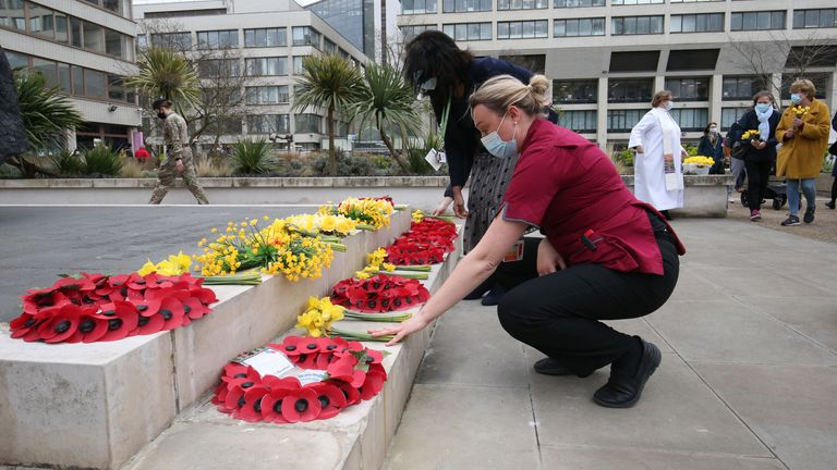 Members of staff places flowers near the statue of Crimean War nurse Mary Seacole during a ceremony to observe a minute's silence at St Thomas' Hospital, central London, during the National Day of Reflection on the anniversary of the first national lockdown to prevent the spread of coronavirus. Picture date: Tuesday March 23, 2021.