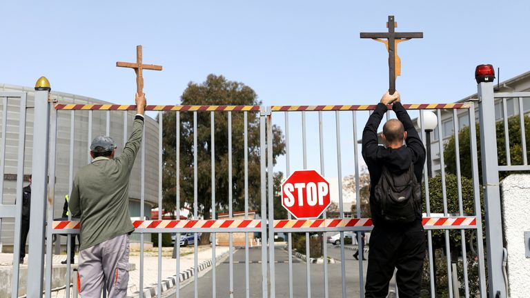 People held crosses at the gates of the Cyprus Broadcasting Corporation in Nicosia