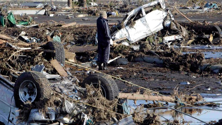 A man looks at the damage caused by an earthquake in Minami Souma City, Fukushima Prefecture