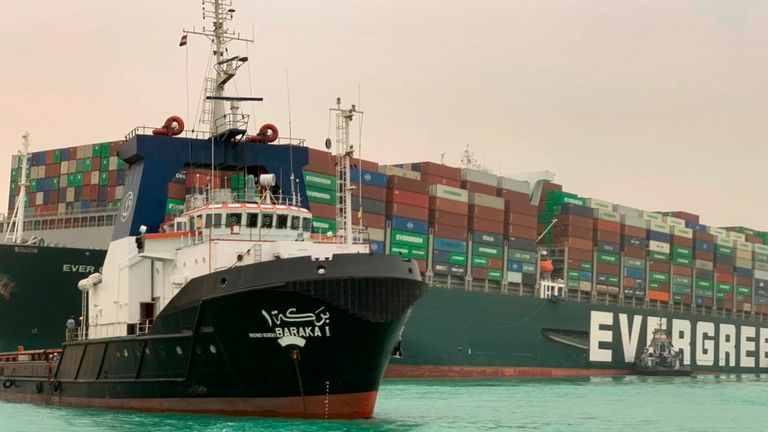 tugboat sails past a container ship named Ever Given