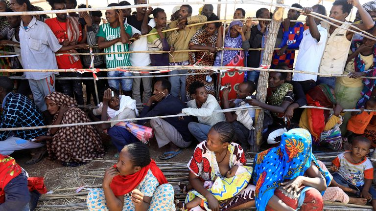 Ethiopians who fled the ongoing fighting in Tigray region gather to receive relief aid at the Um-Rakoba camp on the Sudan-Ethiopia border