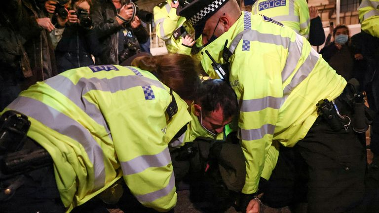Police officers detain a man during a protest