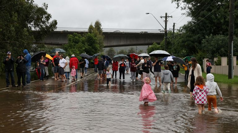 People gather on a flooded residential street near the swollen Nepean River as the state of New South Wales experiences widespread flooding