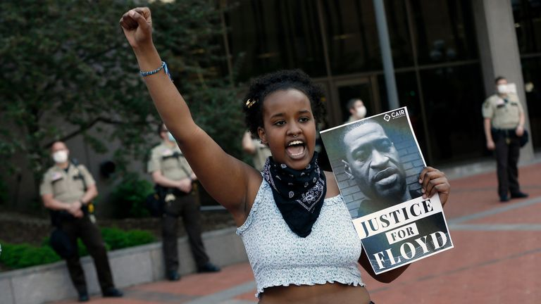 A protester holds a photo of George Floyd during a protest at the Hennepin County Government Center, Thursday, May 28, 2020, as protests continue over the death of George Floyd, who died in police custody Monday night in Minneapolis after video shared online by a bystander showed a white officer kneeling on his neck during his arrest as he pleaded that he couldn't breathe. (AP Photo/Jim Mone)