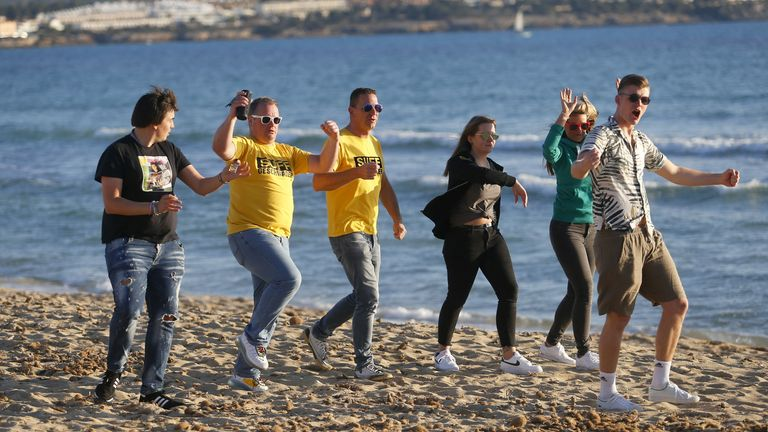 Tourists from Germany dance at El Arenal beach in Palma de Mallorca, following Berlin's lifted quarantine requirement for travelers returning from the Balearic Islands, amid the coronavirus disease (COVID-19) pandemic, Spain March 21, 2021