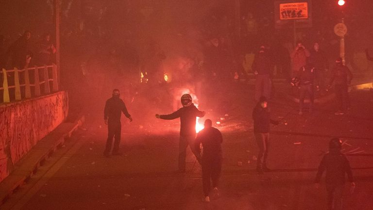 Flares burn near protesters as they clash with police officers in Athens
