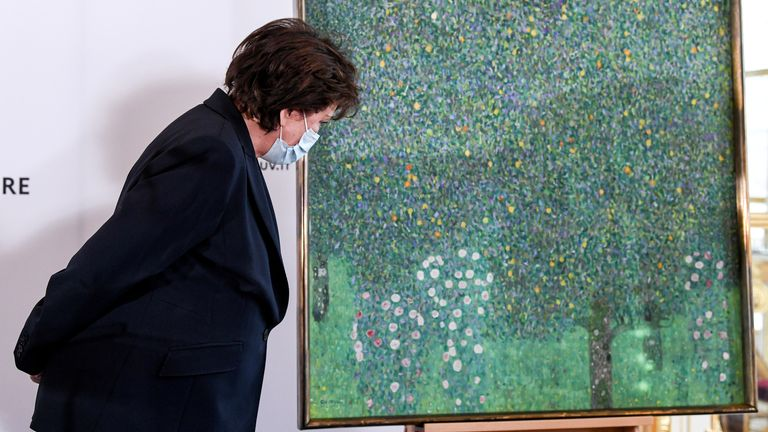 """French Culture Minister Roselyne Bachelot stands next to the painting """"Rosebushes under the Trees"""" by Austrian painter Gustav Klimt"""