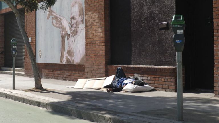 A homeless man sleeping on the pavement outside the headquarters of BetterUp