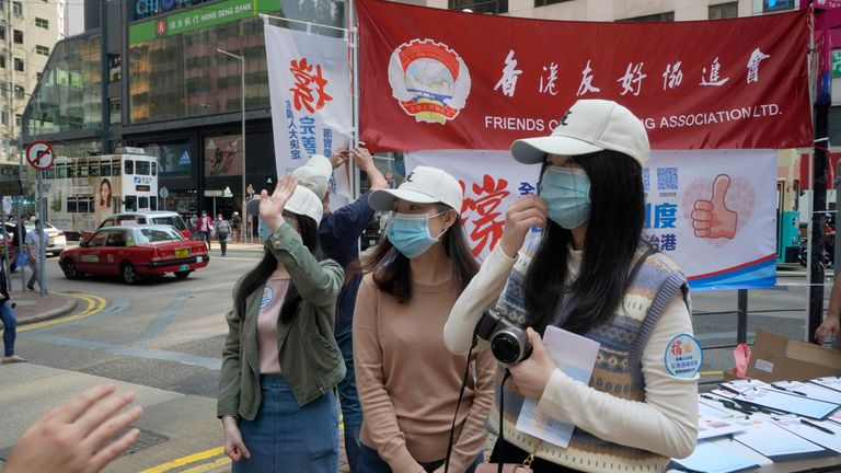 Pro-China staff members collect signatures supporting changes to election rules in Hong Kong