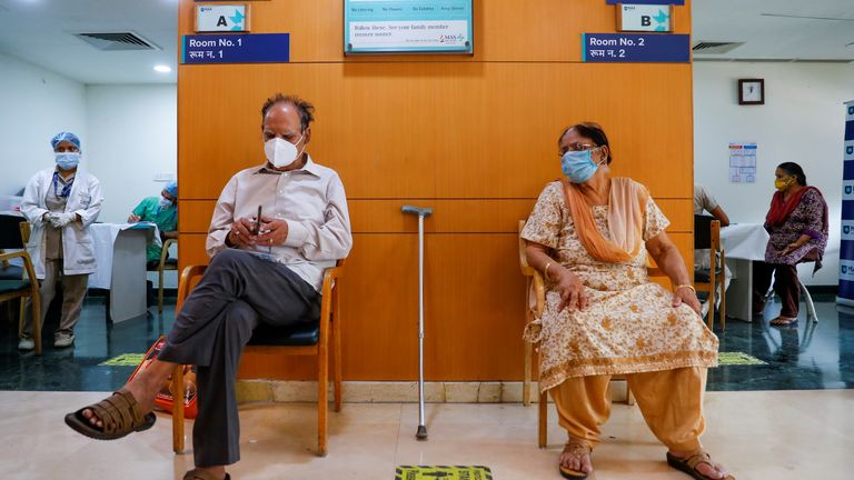 An elderly couple waits for their turn as they sit outside a vaccination room, at Max Super Speciality Hospital, amid the coronavirus disease (COVID-19) pandemic, in New Delhi, India, March 17, 2021. REUTERS/Adnan Abidi