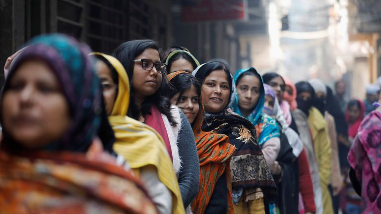 Voters, many not wearing masks, stand in a queue outside a polling booth in New Delhi